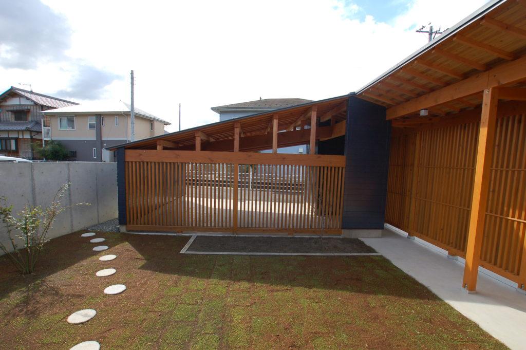 三方道路に囲まれたプライバシー確保が難しい敷地に格子で囲まれた入り江のような庭を持つ家