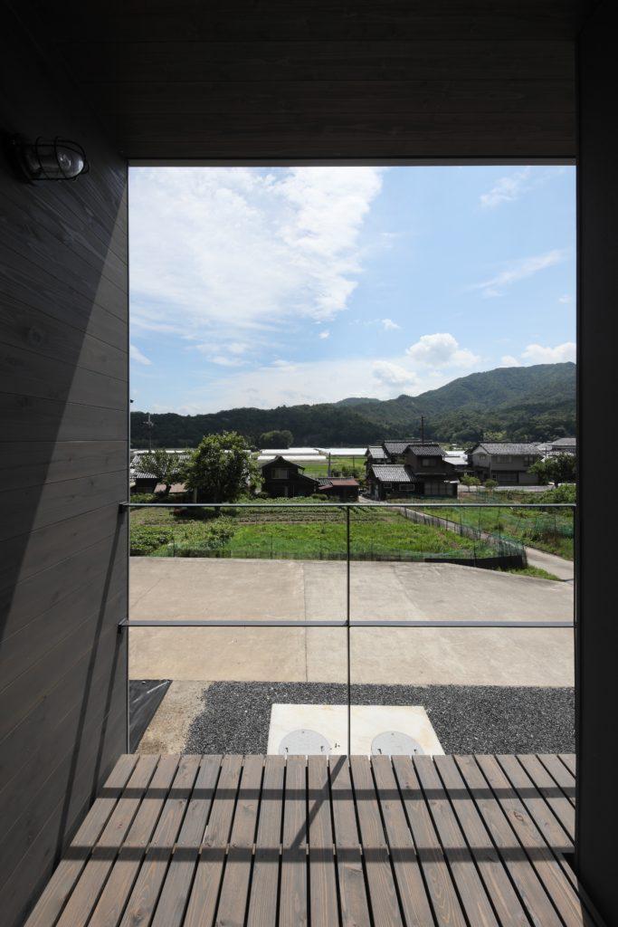 緩やかな曲線を描く山並みと透き通るような空を切り取った景観を眺める家