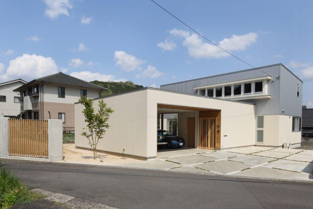 道路からの視線をガレージで遮りながら開放的なリビングから愛車たちを眺められるように考えられた家