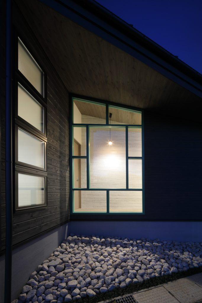 道路に面したガレージと住居の間に庭を持つ 角地に面した敷地の空間利用が特徴の平屋の家