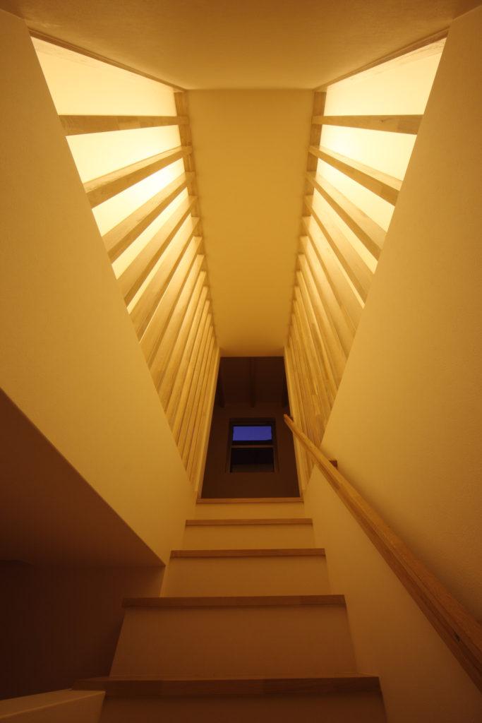 白い二つのL型を組み合わせたフォルムが特徴のプライベートガーデンを持つ家