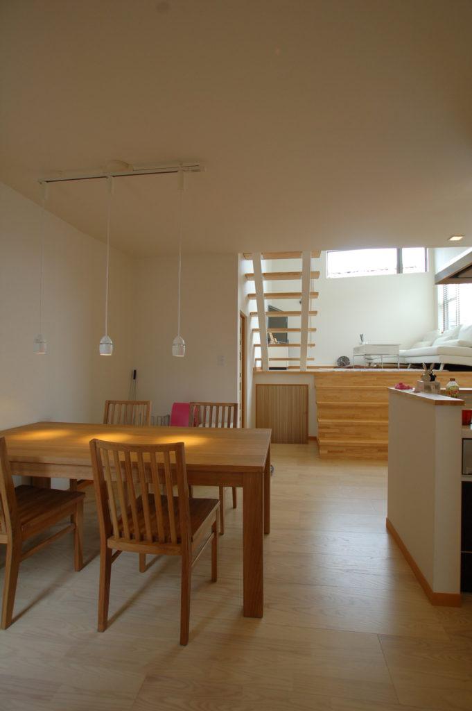 家の中に光を取り込む中二階リビングを持つモスグリーンのフォルムが特徴の家