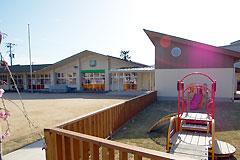 子どもたちがのびのびと遊ぶ芝生の庭とデッキを備えた乳児棟の増築